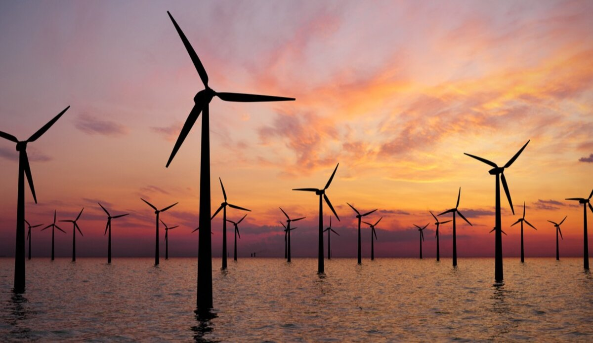 A series of wind turbines against a sunset
